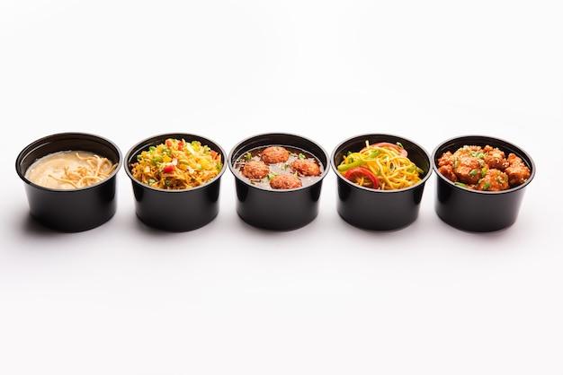 Grupa dostarczanych do domu indyjsko-chińskich potraw w plastikowych opakowaniach, pojemnikach lub pudełkach zawierających makaron schezwan, smażony ryż, kurczaka chili, mandżurkę i zupę.