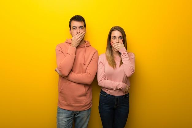 Grupa dwóch ludzi na żółtym tle obejmujące usta rękami