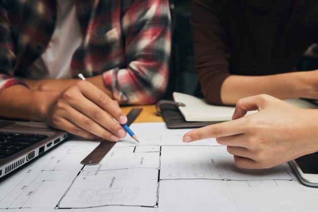 Grupa dwóch współpracowników pracujących z planem w biurze. koncepcja współpracy zespołowej.