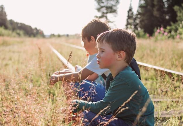 Grupa dzieci animuje na kolei na zmierzchu