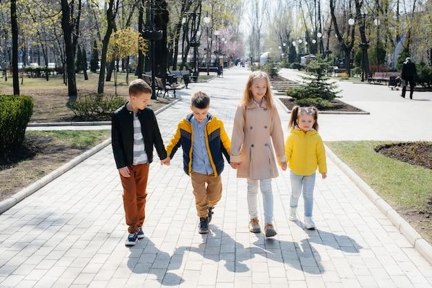 Grupa dzieci bawi się razem i spaceruje po parku trzymając się za ręce