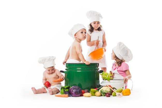 Grupa dzieci bawią się i gotują z warzywami. mali kucharze na białym tle na koncepcji zdrowego odżywiania