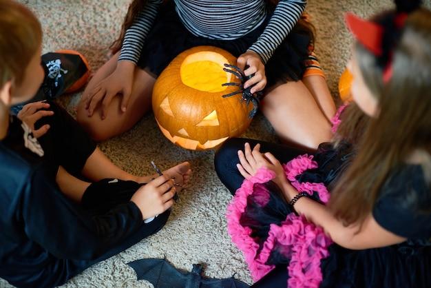 Grupa dzieci bawiące się dyni na halloween