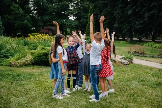 Grupa dzieci biega latem, bawi się i bawi się w większym zespole w lecie w parku