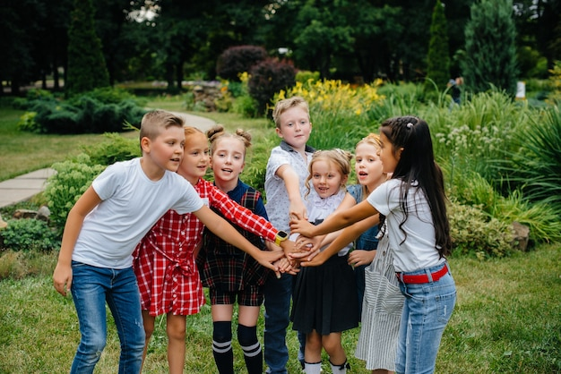 Grupa dzieci biegnie, bawi się i bawi latem w parku jako większy zespół. szczęśliwe dzieciństwo.