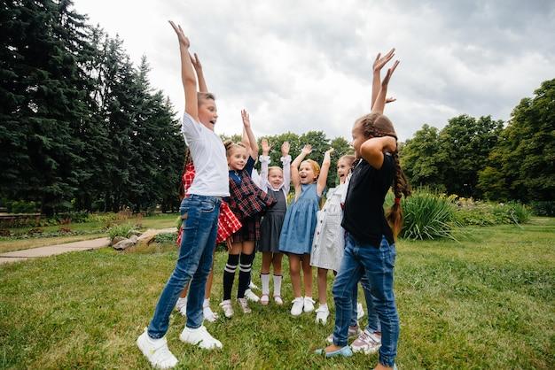 Grupa dzieci biegnie, bawi się i gra latem w parku jako większy zespół. szczęśliwe dzieciństwo.