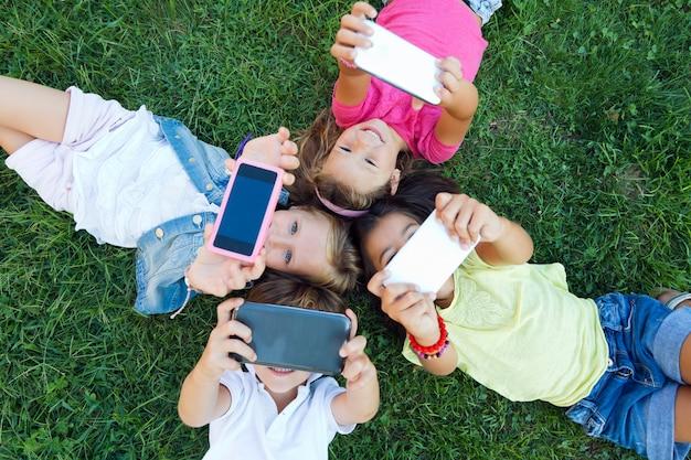 Grupa dzieci biorących selfie w parku.