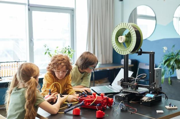 Grupa dzieci budujących robota i korzystających z drukarki 3d podczas zajęć inżynierskich w szkole, kopia przestrzeń