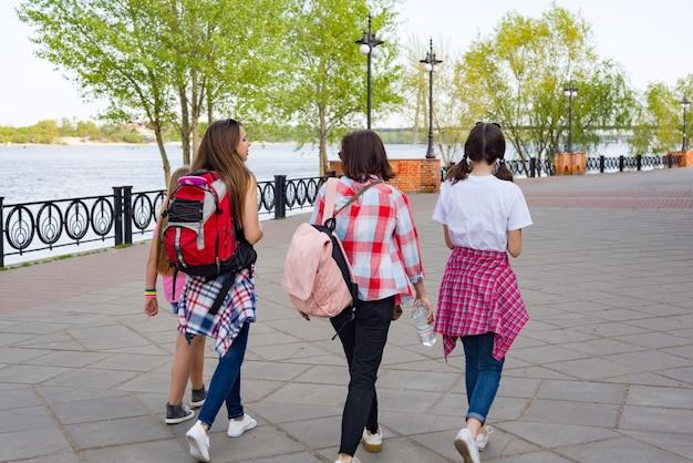 Grupa dzieci i kobiet chodzących w parku.
