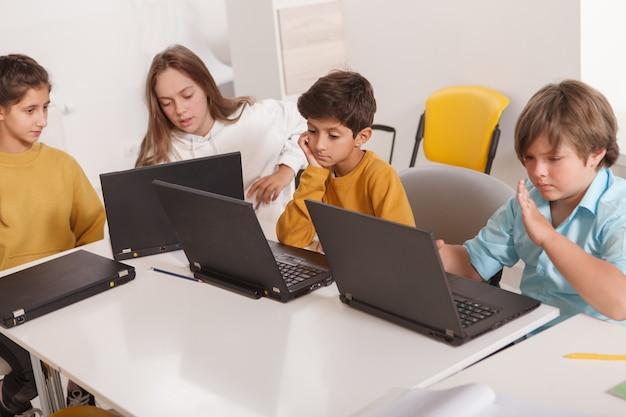 Grupa dzieci korzystających z laptopów, pracujących nad szkolnym projektem