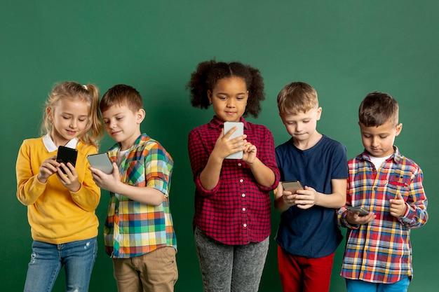 Grupa dzieci korzystających z telefonów