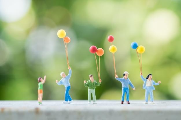 Grupa dzieci miniaturowe postacie ludzi z kolorowym balonem z zieloną przyrodą.