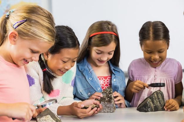 Grupa dzieci patrząc na okaz kamień przez szkło powiększające