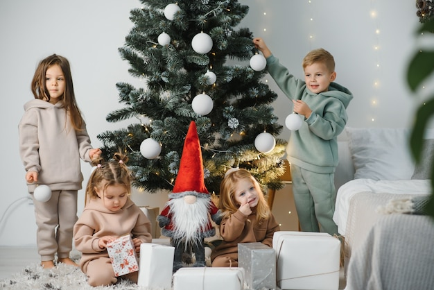 Grupa dzieci pod choinką w domu. chłopcy i dziewczęta w fantazyjnych strojach świętują ferie zimowe. dzieci otwierają prezenty przy kominku.
