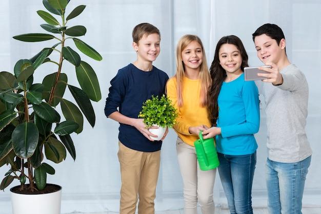 Grupa dzieci, podlewanie kwiatów i selfie