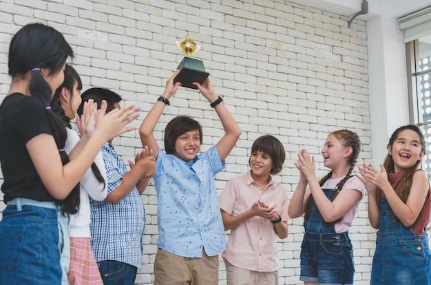 Grupa dzieci pogratulowała szczęśliwej chłopiec trzyma trofeum filiżanki nagrodę jego wygrana w sala lekcyjnej
