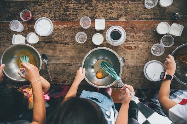 Grupa dzieci przygotowuje piekarnię w kuchni. dzieci uczą się gotować ciasteczka