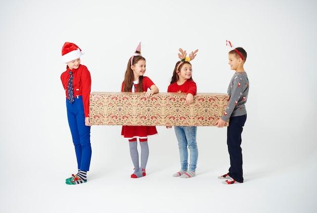 Grupa dzieci przygotowuje się trzymając duże pudełko na prezent