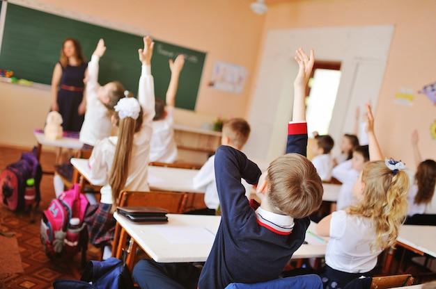 Grupa dzieci siedzi przy biurkach
