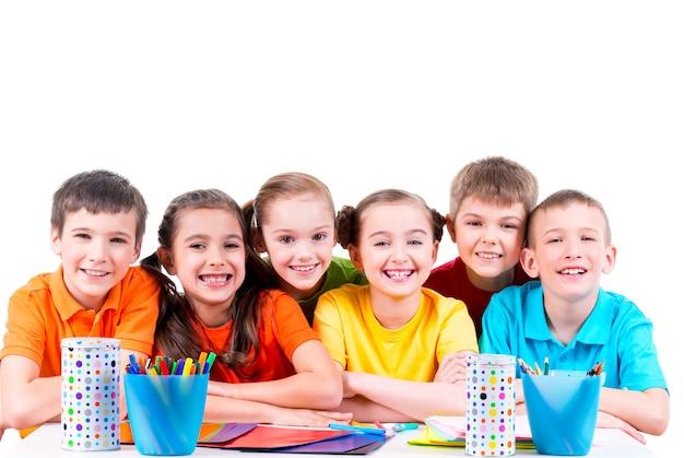 Grupa dzieci siedzi przy stole z markerami, kredkami i kolorowym kartonem.