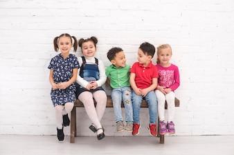 Grupa dzieci siedziała na ławce