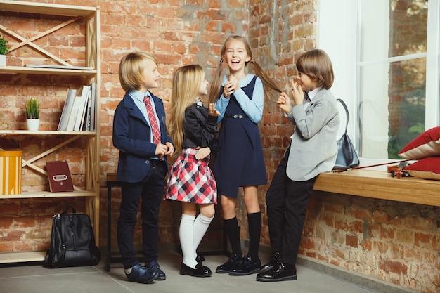 Grupa dzieci spędzających razem czas po szkole. przystojni przyjaciele odpoczywają po zajęciach przed rozpoczęciem odrabiania lekcji. nowoczesne wnętrze loft. czas szkolny, przyjaźń, edukacja, koncepcja wspólnoty.