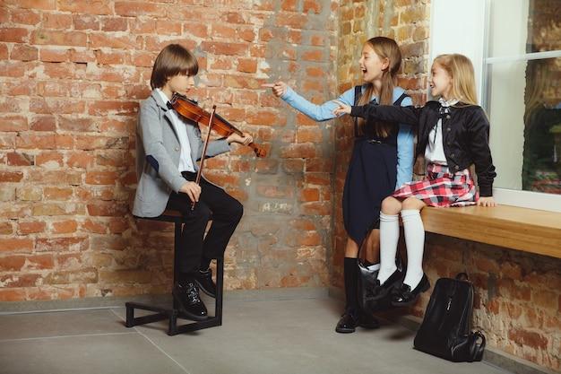 Grupa dzieci spędzających razem czas po szkole. przystojni przyjaciele odpoczywają po zajęciach przed rozpoczęciem odrabiania lekcji. nowoczesne wnętrze loftu. czas szkolny, przyjaźń, edukacja, koncepcja wspólnoty.