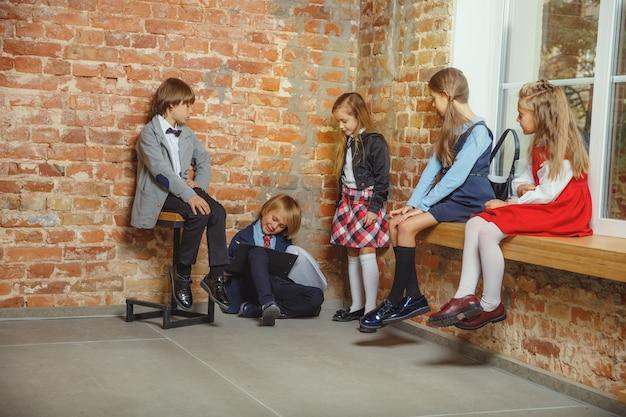 Grupa dzieci spędzających razem czas po szkole. przystojni przyjaciele odpoczywają po zajęciach przed rozpoczęciem odrabiania lekcji