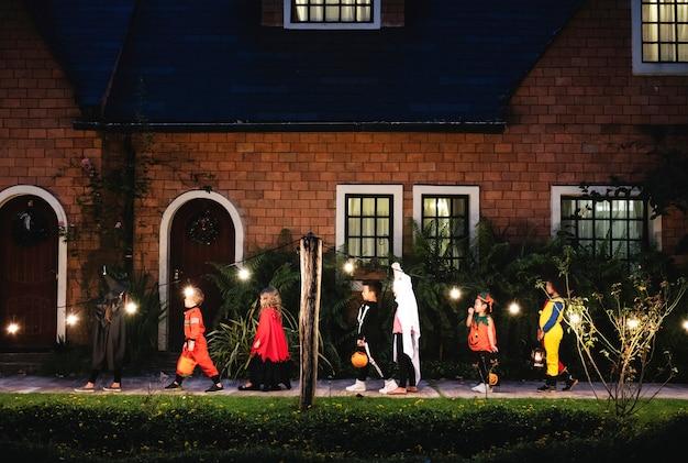 Grupa dzieci w kostiumach na halloween chodzących, by oszukać lub leczyć