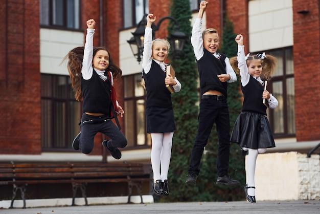Grupa dzieci w mundurkach szkolnych, skoki i wspólna zabawa na świeżym powietrzu w pobliżu budynku edukacji.