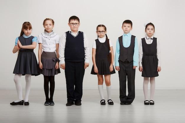 Grupa dzieci w mundurkach w studio na białym tle. edukacja, moda, pojęcie przyjaźni.