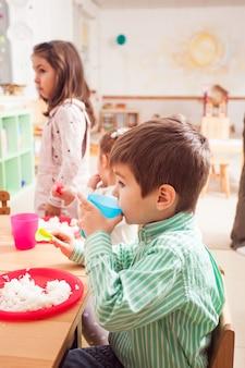 Grupa dzieci w przedszkolu siedząca przy drewnianym stole i jedząca ryż