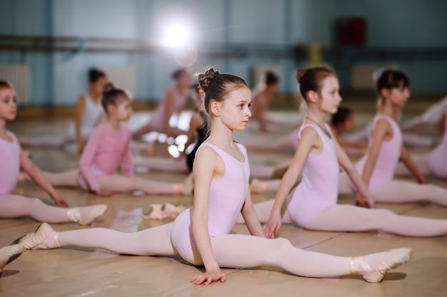 Grupa dzieci w szkole baletowej lub w sekcji gimnastycznej na dywanach carimat wykonuje ćwiczenia