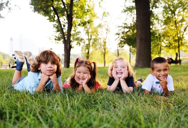 Grupa dzieci w wieku przedszkolnym bawiące się w parku na trawie