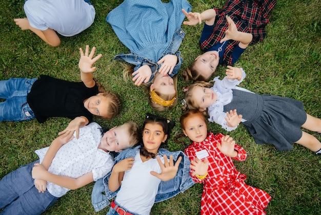 Grupa dzieci w wieku szkolnym leży na trawie w kręgu i dobrze się bawi