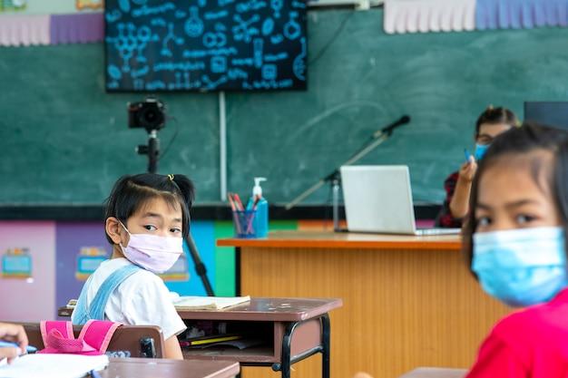 Grupa dzieci w wieku szkolnym noszących maskę medyczną lub maskę chirurgiczną w celu ochrony przed wirusem uczy się w klasie, ochrony covid-19 i zakażenia koronawirusem.