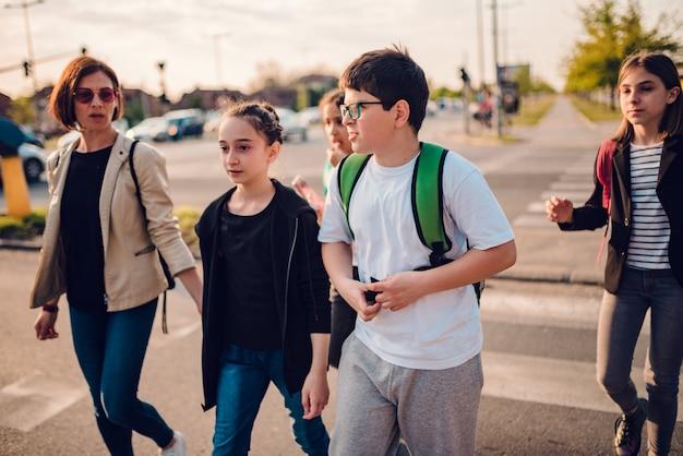 Grupa dzieci w wieku szkolnym przez jezdnię