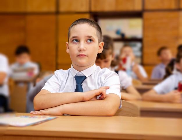 Grupa dzieci w wieku szkolnym, słuchając nauczyciela w klasie