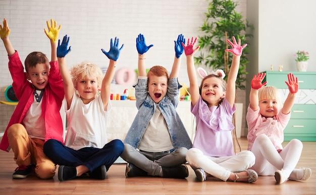 Grupa dzieci z kolorowymi, malowanymi dłońmi
