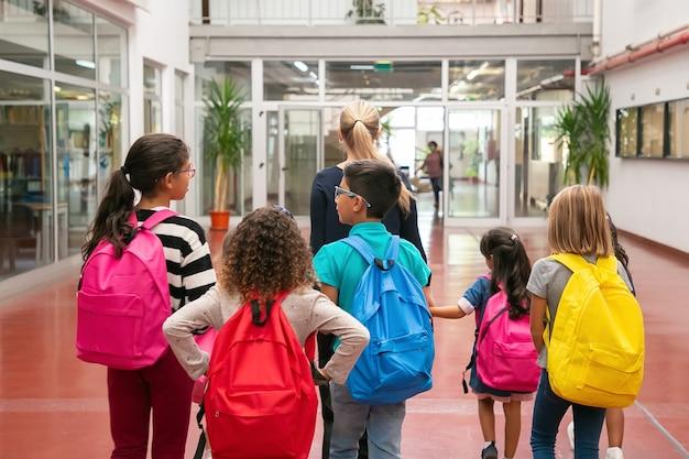 Grupa dzieci z nauczycielką spaceru w szkolnym korytarzu