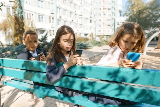 Grupa dzieci z telefonami komórkowymi