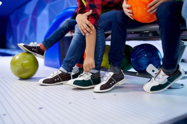 Grupa dzieci zakłada buty do kręgli na ławce