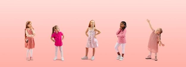 Grupa dzieci ze szkoły podstawowej lub uczniów w kolorowych ubraniach na co dzień w różowym studio