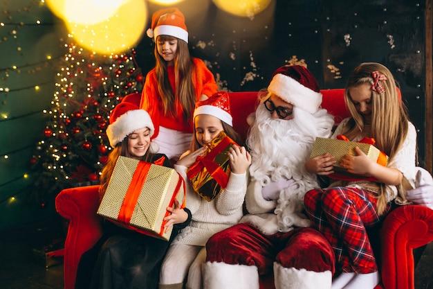 Grupa dzieciaki siedzi z santa i teraźniejszość na wigilii