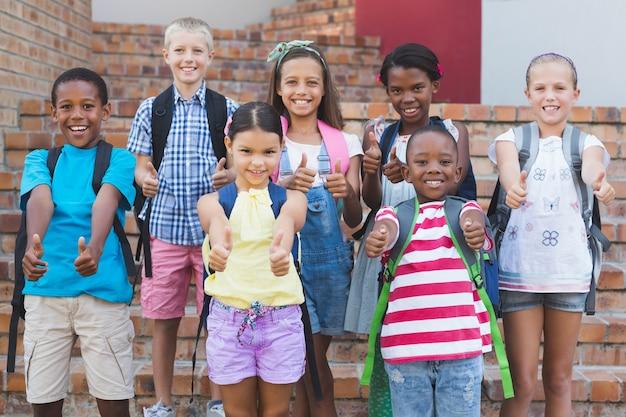 Grupa dzieciaki stoi na schody pokazuje aprobaty
