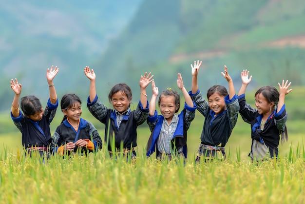 Grupa dziewcząt na obszarach wiejskich w wietnamie śpiew i taniec na tarasach ryżowych ich sąsiedztwo w mu cang chai, yenbai, wietnam