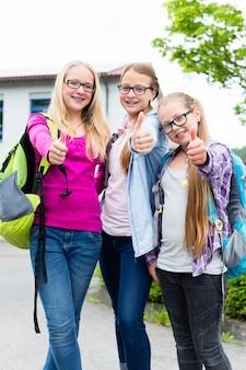 Grupa dziewcząt stojących przed szkołą