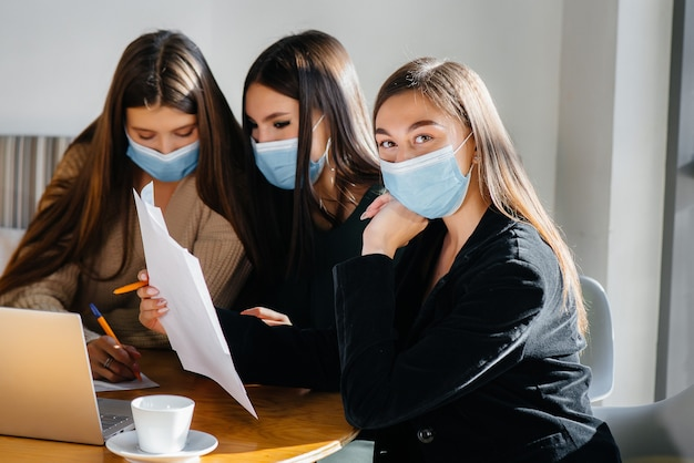 Grupa dziewcząt w maskach siedzi w kawiarni i pracuje na laptopach. nauczanie studentów.