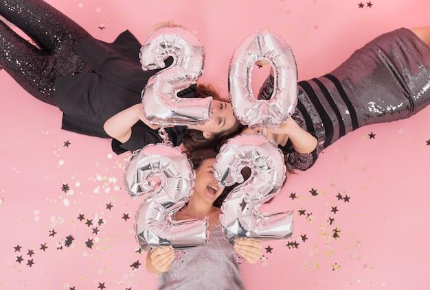 Grupa dziewczyn bawi się na przyjęciu bożonarodzeniowym, leżąc na różowym tle z balonami z cyframi 2022.