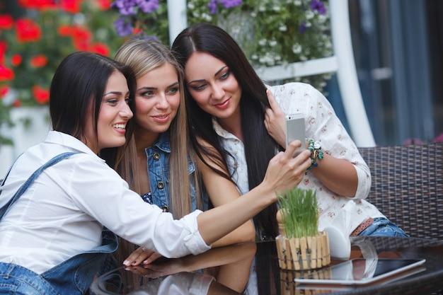 Grupa dziewczyn robi selfie fotografii przy mobilnym aparatem ono uśmiecha się. ładne kobiety zabawy w kawiarni. młode dziewczyny się śmieją